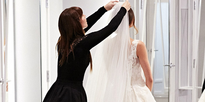 Brides holding hands and dancing in David's Bridal dressing room area