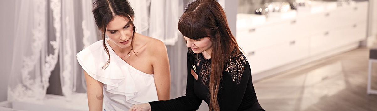 Bride sitting with David's Bridal stylist looking through booklet