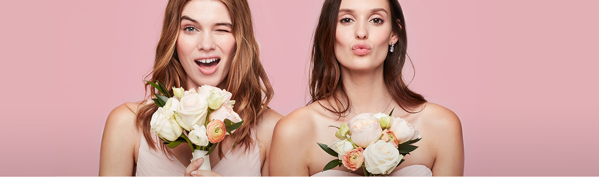 Bridesmaids holding bouquets winking and blowing kisses to the camera