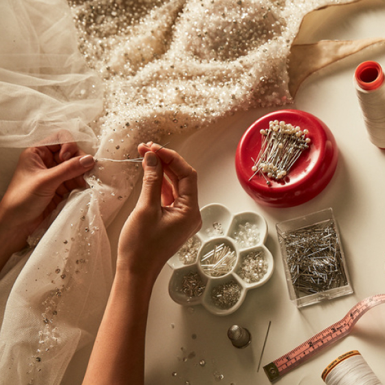davids bridal alterations expert sewing beading on wedding dress.