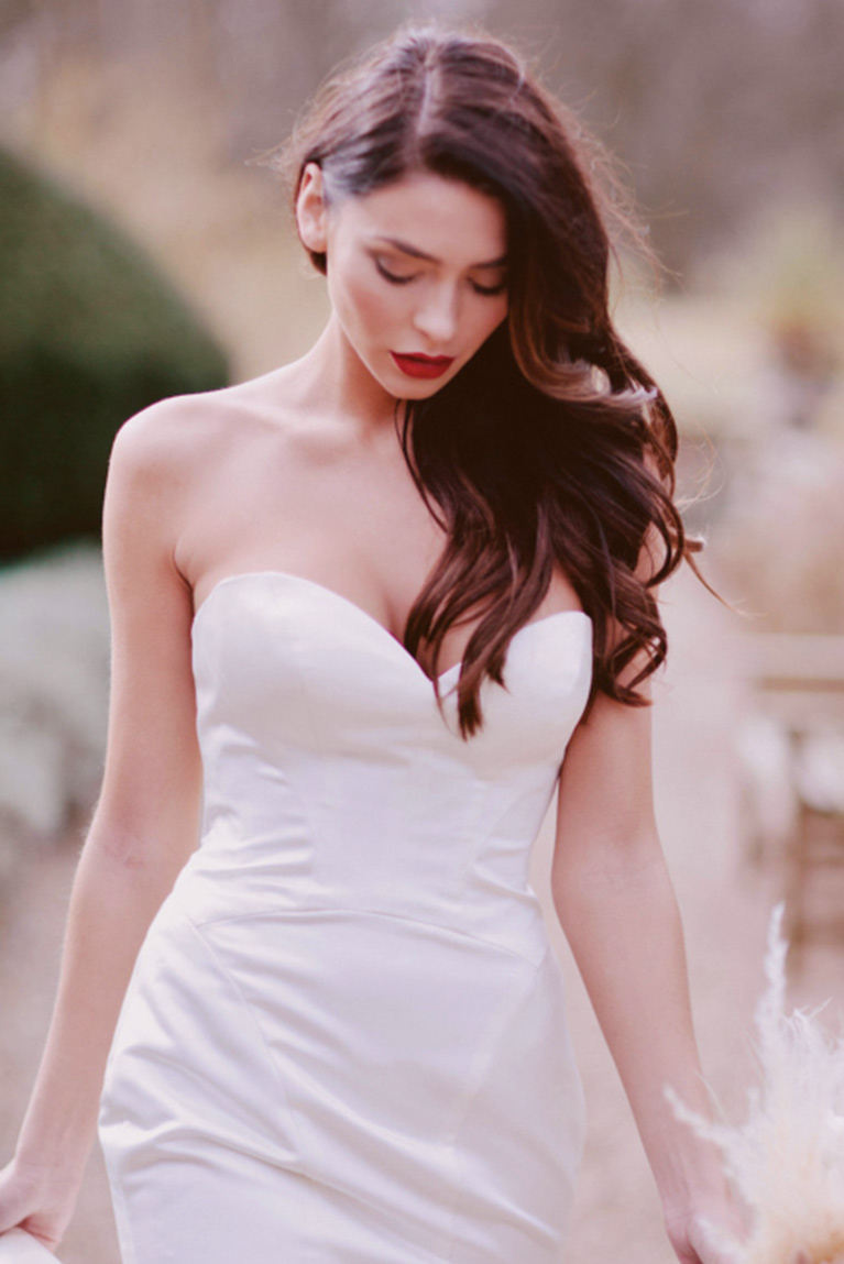 Bride in form fitting satin wedding dress with sweetheart neckline