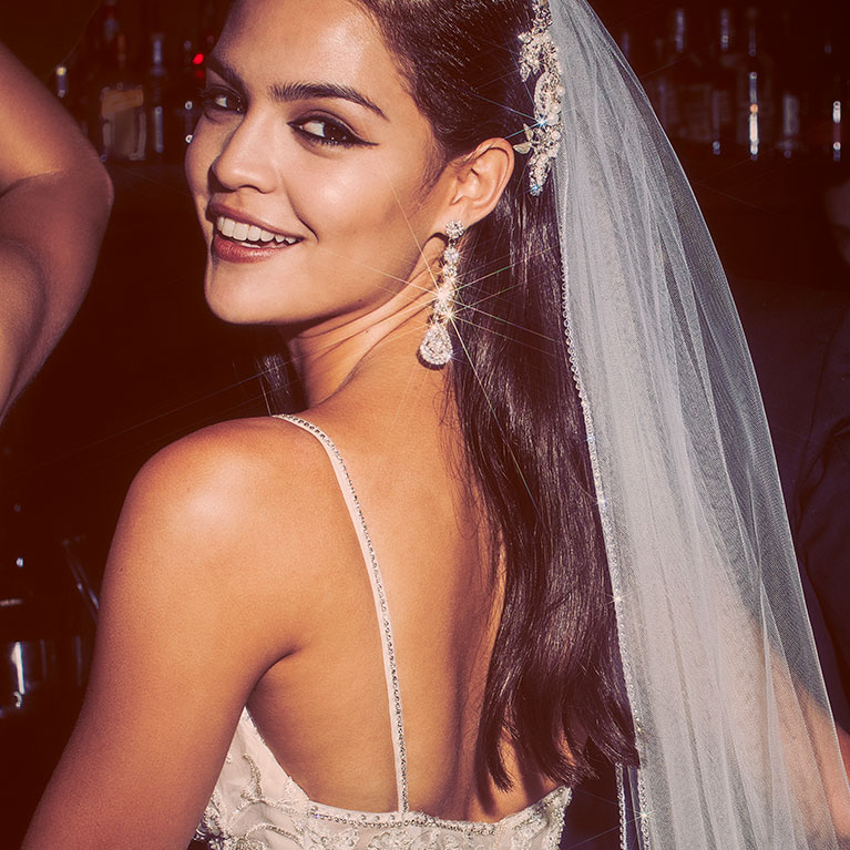 Bride wearing veil with sparkly hairpiece and long earrings.