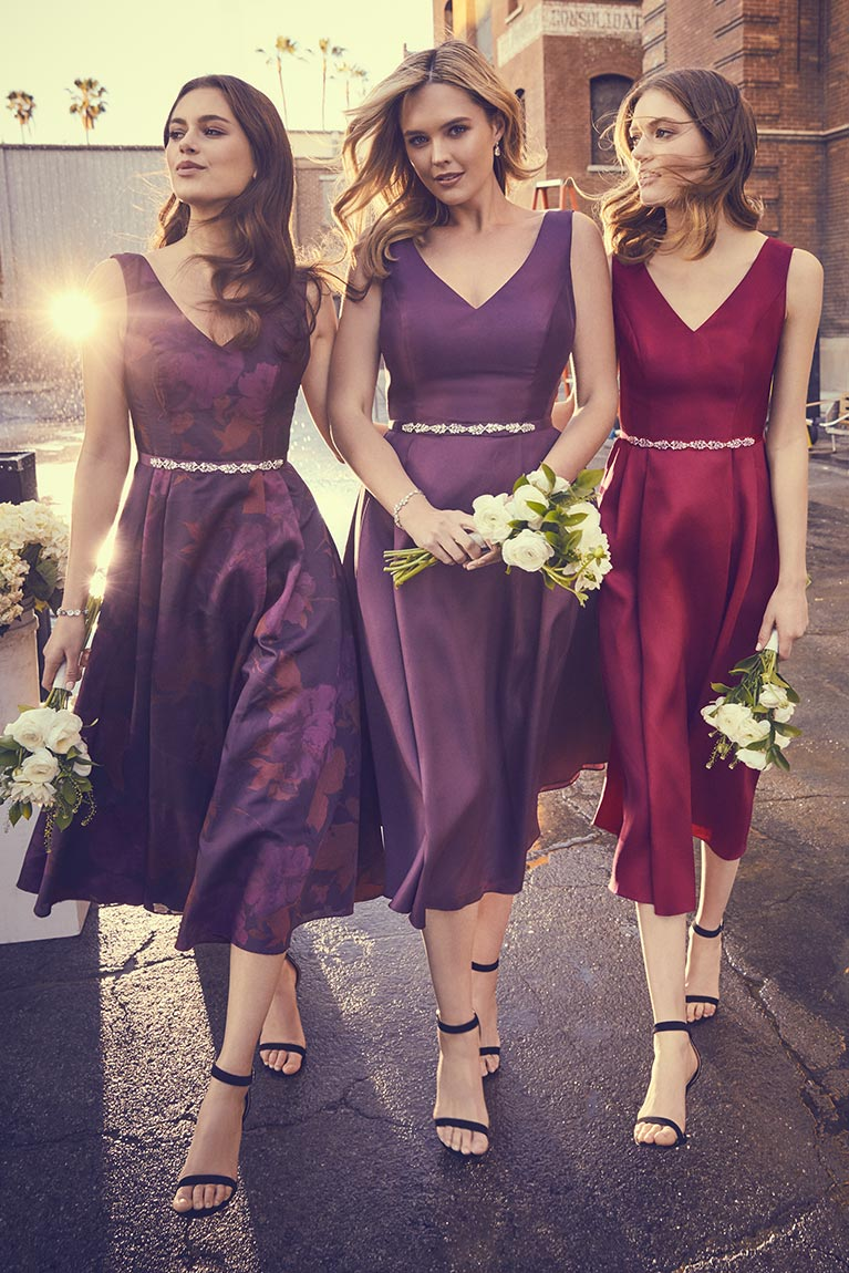 Bridesmaids wearing mismatched wine colored bridesmaid dresses.