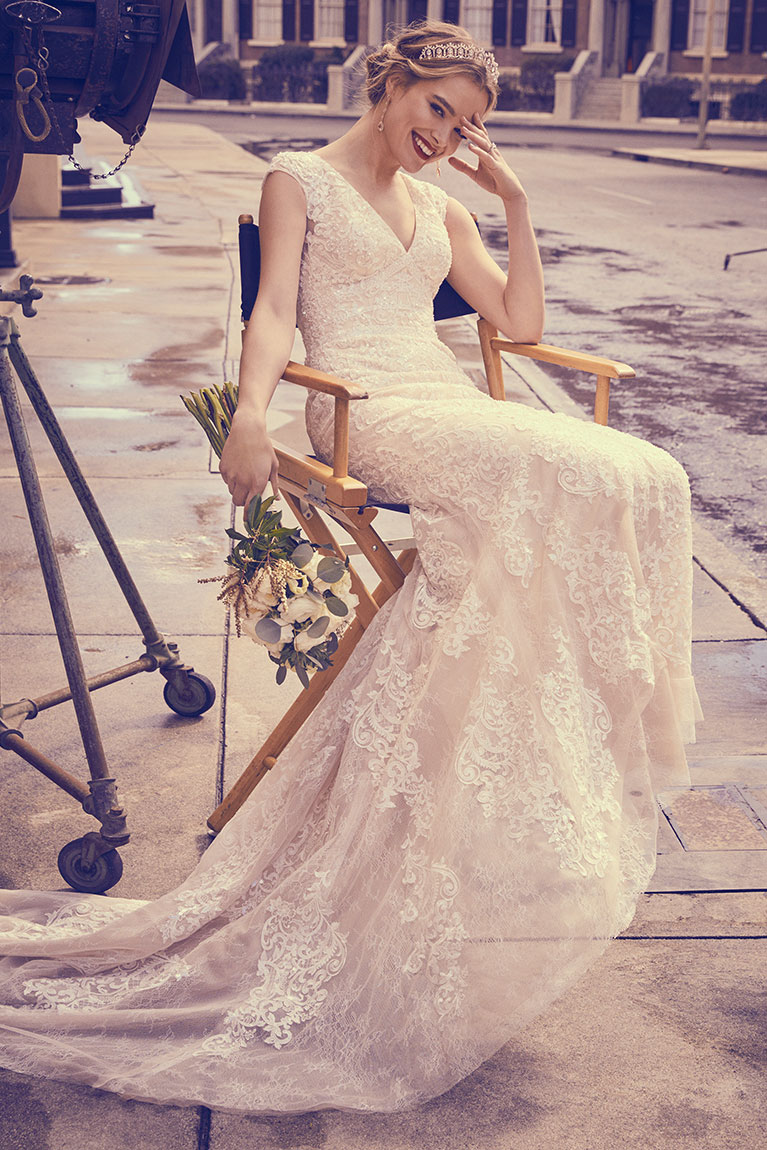 Bride sitting in chair wearing long v-neck Oleg Cassini wedding gown