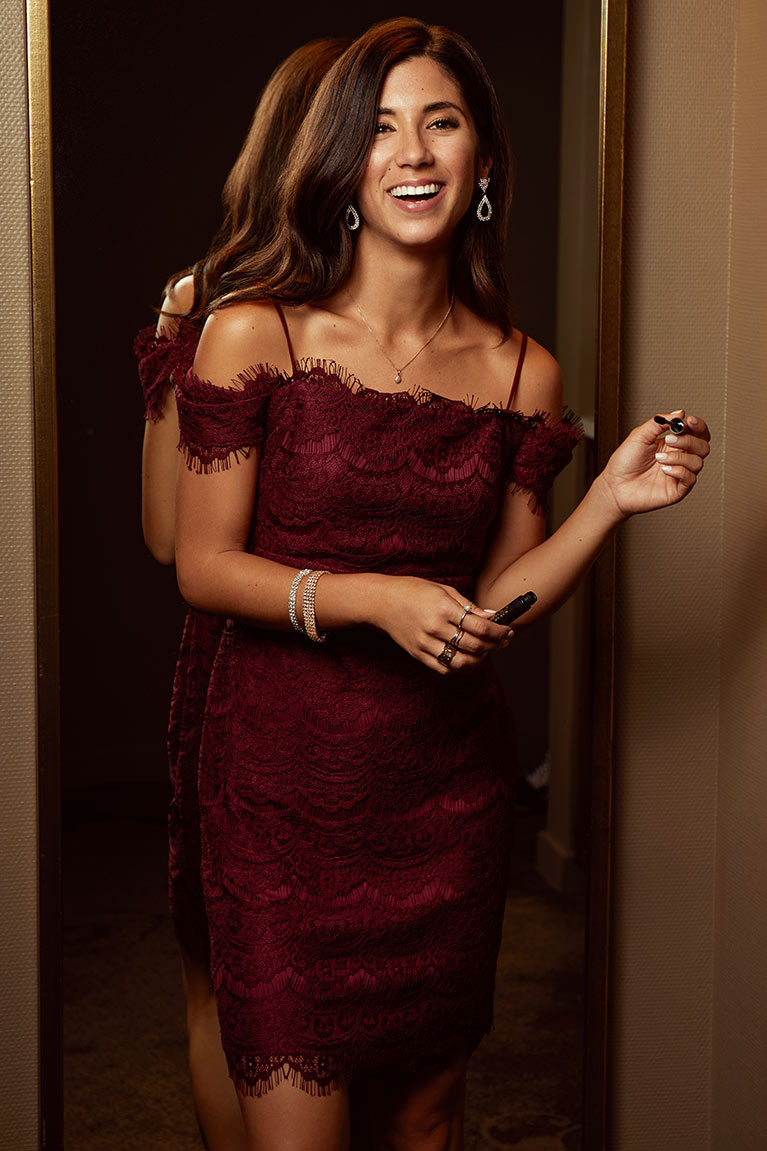 Woman in wine colored cold shoulder lace dress standing against mirror