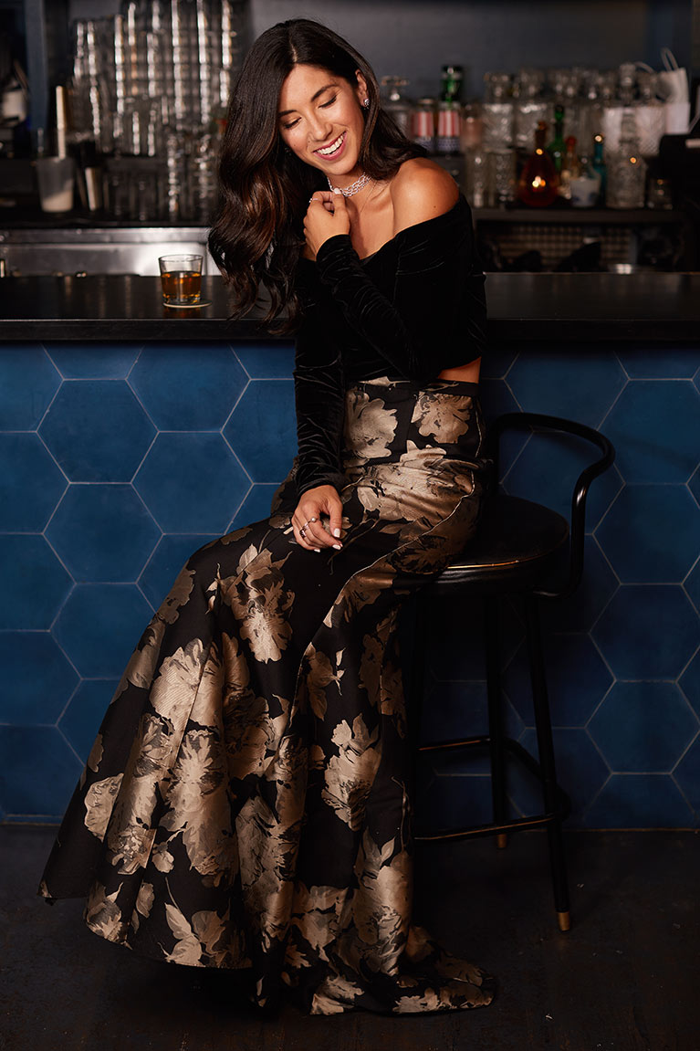 Woman in an off the shoulder black top and gold printed floor length skirt sitting on barstool