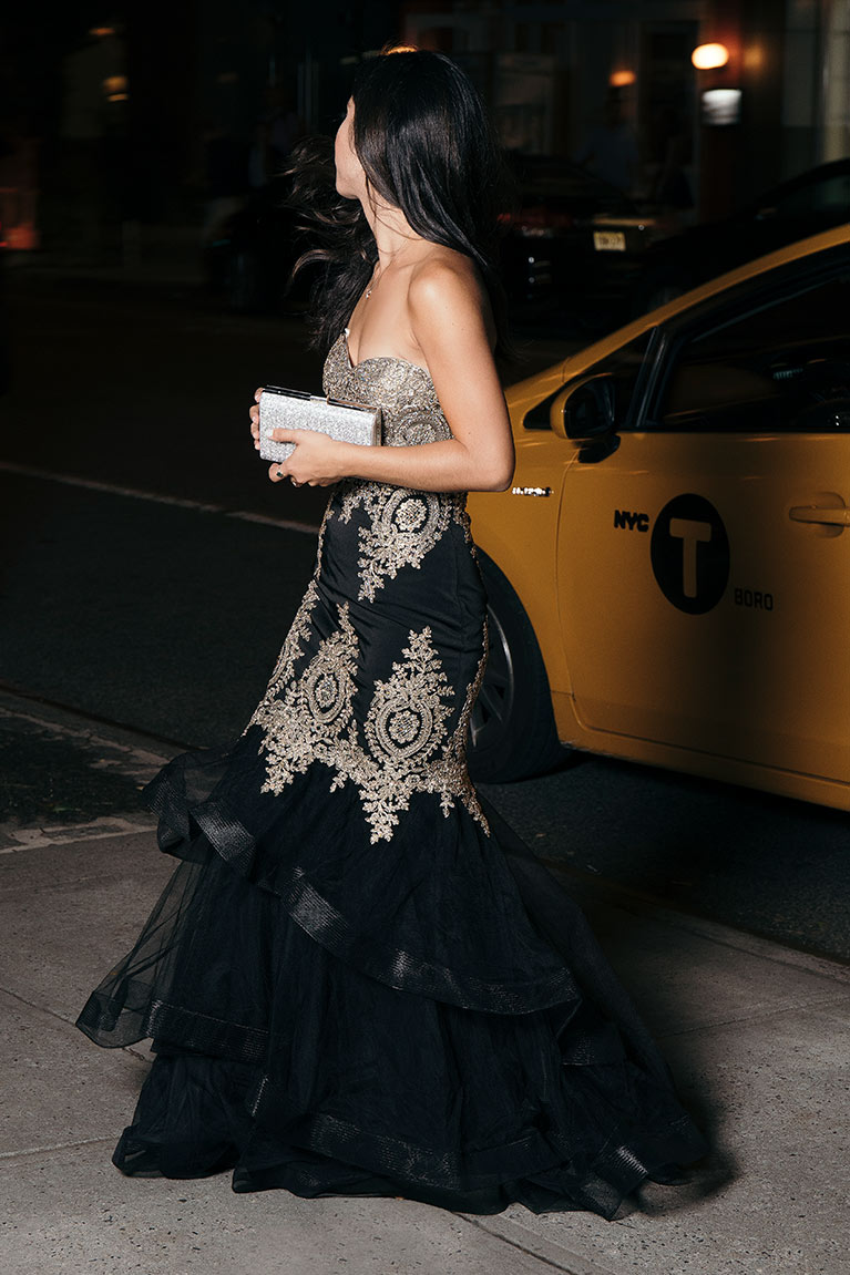 Woman walking away from taxi cab in gold and black embroidered mermaid gown