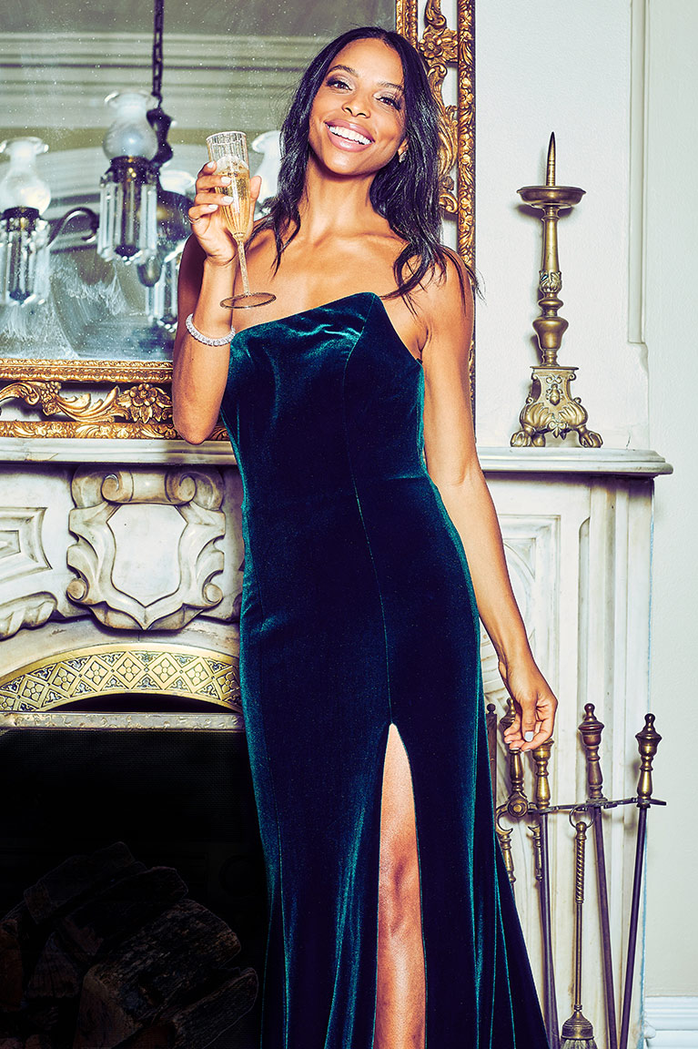 9c0976e14c9 Woman in green velvet dress standing by fireplace with champagne. A new ...