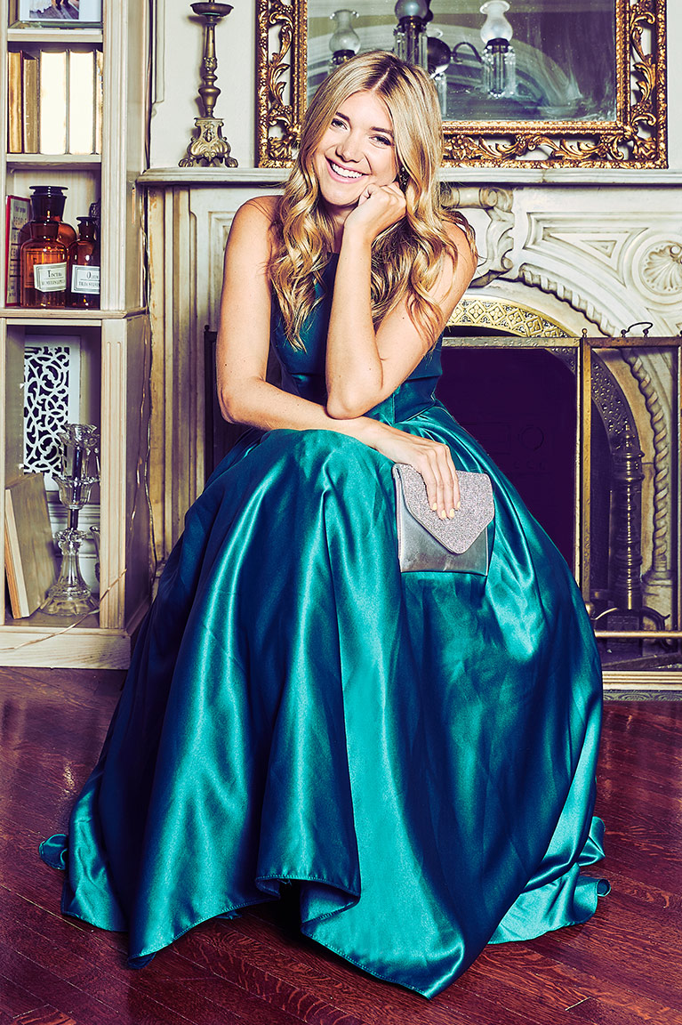 a654304bbd Woman in satin green dress sitting by fireplace holding a clutch