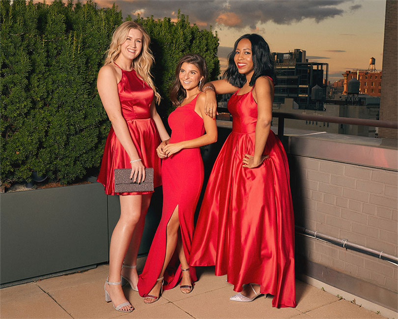 Three girls wearing red holiday dresses.