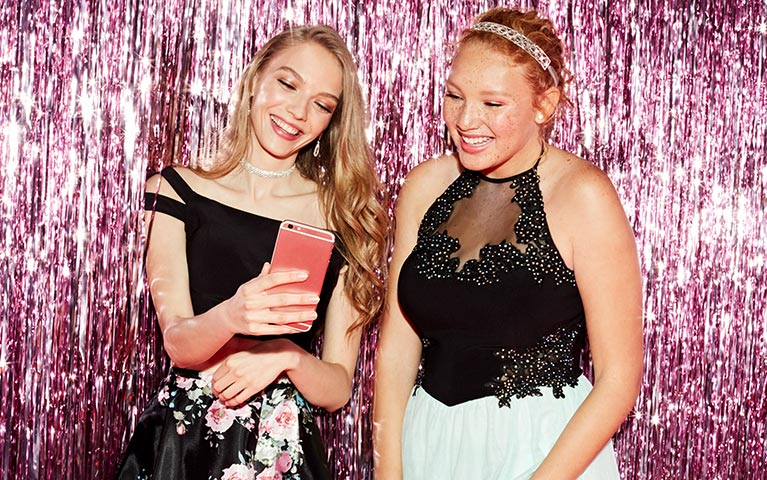 Girls taking pictures at their homecoming dance.