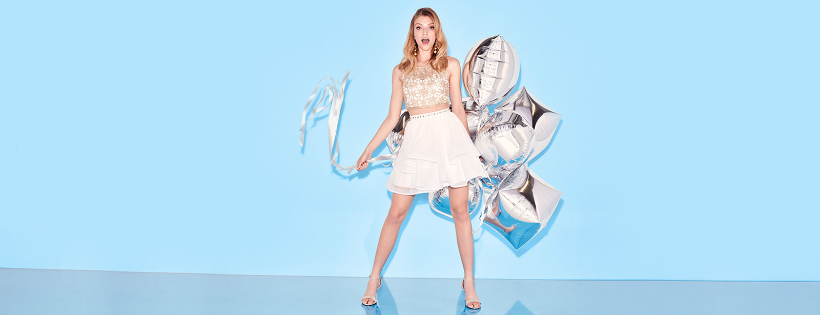Homecoming Girl in white skirt and crop top holding silver balloons