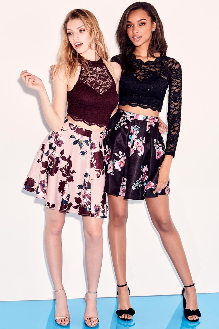Two homecoming girls wearing floral skirts and lace crop tops