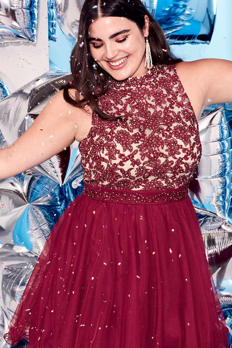 Homecoming girl in wine colored dress dancing and smiling