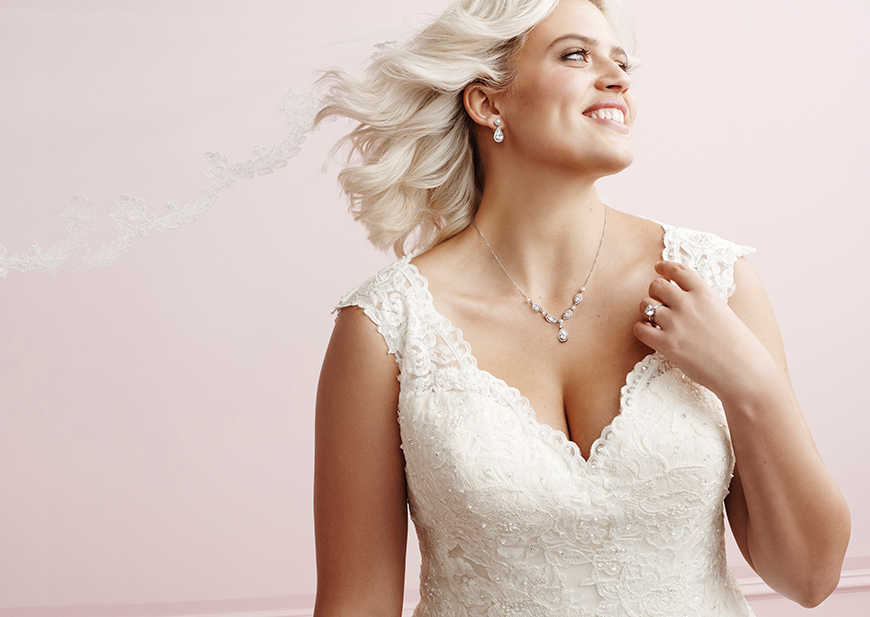 Plus size bride wearing off-the-shoulder wedding dress and floral hair accessory