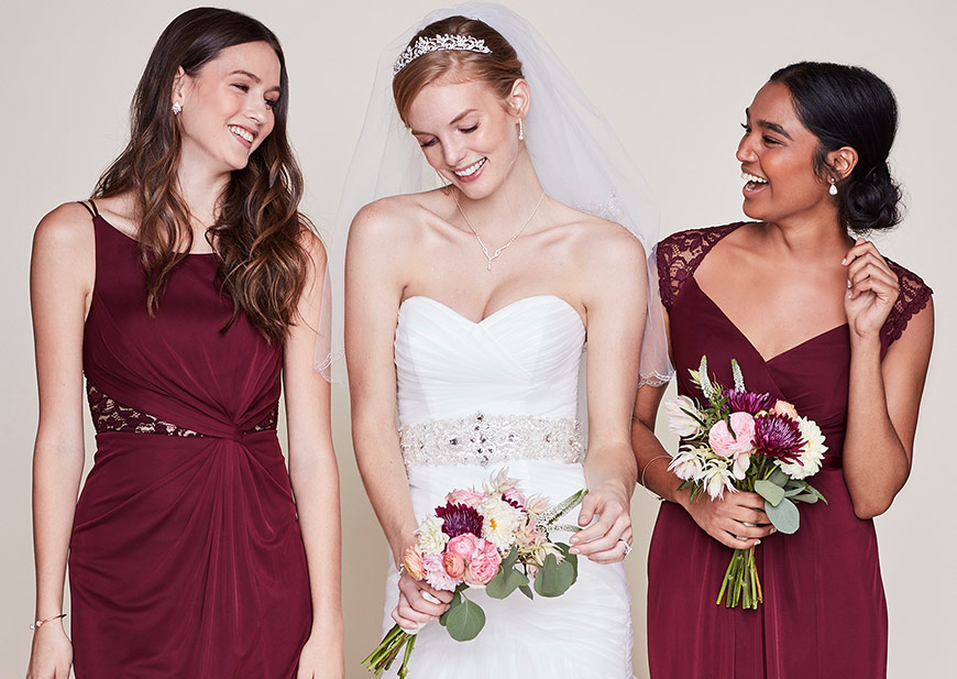 Bride with bridesmaids wearing wine dresses and sparkling earrings