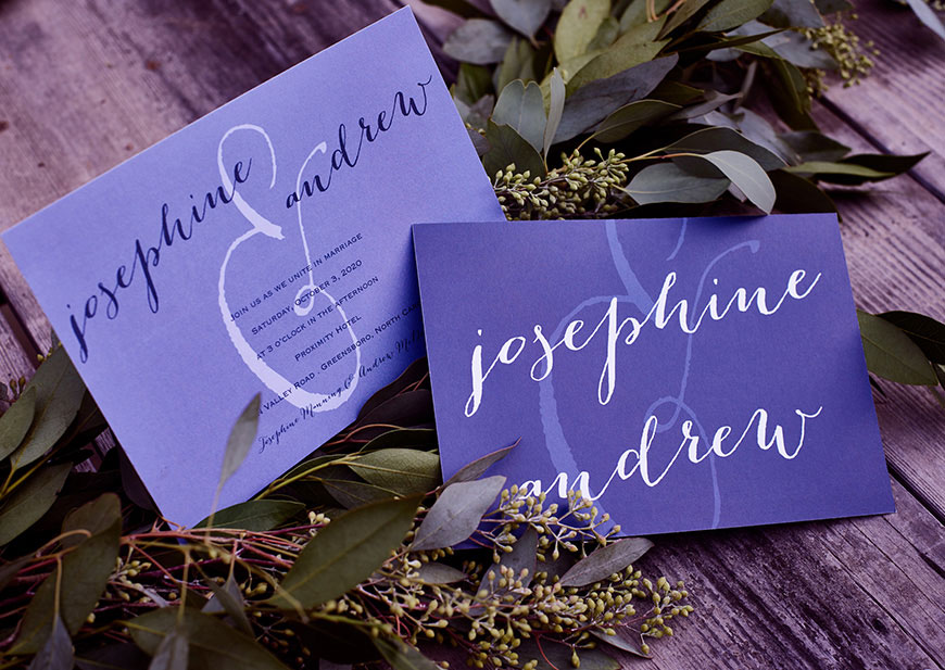 Front and back of purple wedding invitations on wood table with greenery