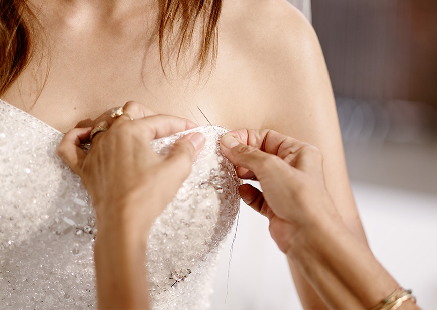 Seamstress assisting bride with wedding dress alterations