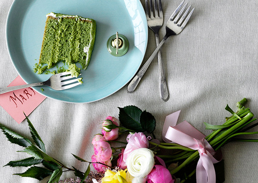 Light blue plate with green cake and forks on table with flowers and seating card