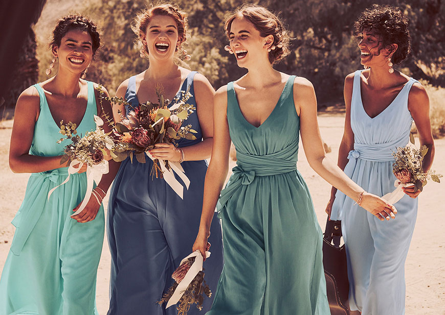 Happy bridesmaids in long flowing dress style featuring a mix of blue hues
