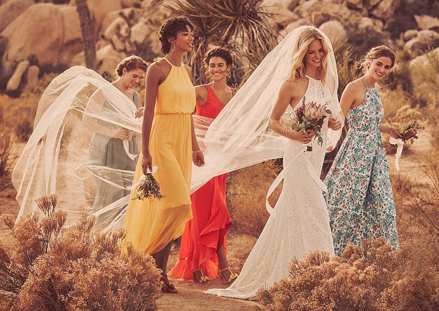 Bride with veil flowing at outdoor wedding with eclectic bridesmaids