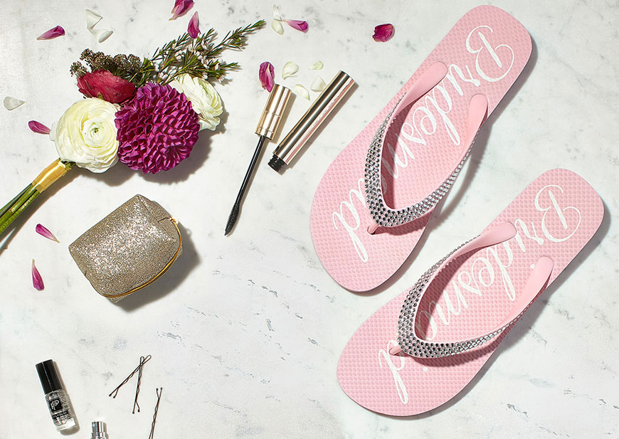 Tabletop with bride rhinestone flip-flops, makeup, hair pins, case and flowers
