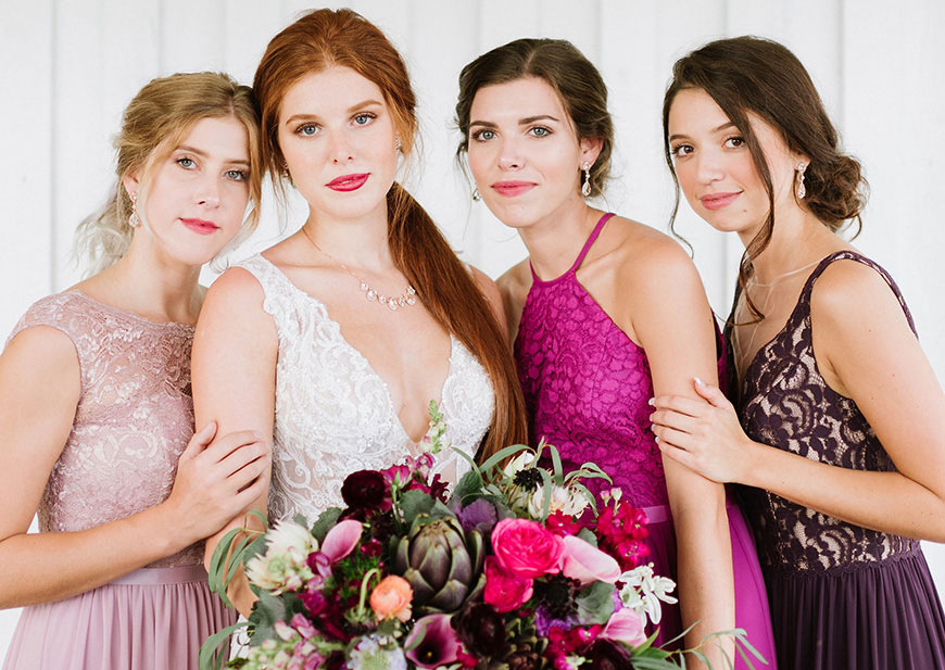 Bride with big colorful bouquet and bridesmaids in colorful lace dresses