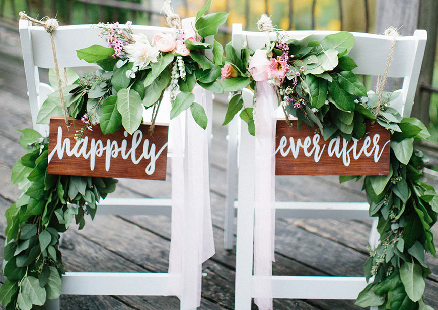 Wedding chairs decorated with greenery, flowers and Happily Ever After sign