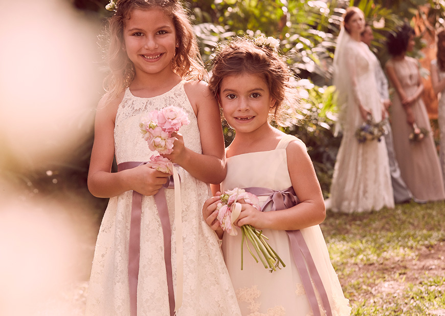 Flower girls with purple ribbons at outdoor wedding