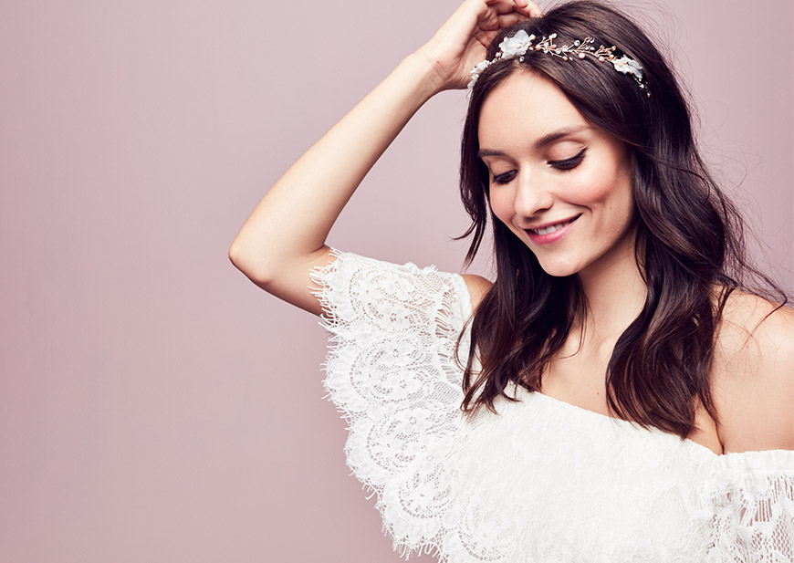 Bride wearing lace off-the-shoulder dress and floral headband in long hair