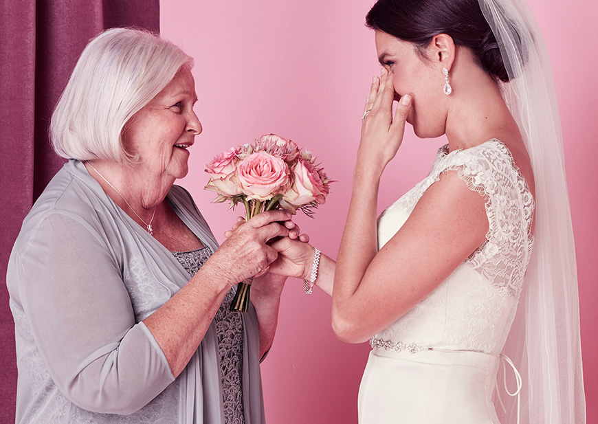 Happy tears from bride holding hands with grandmother on wedding day