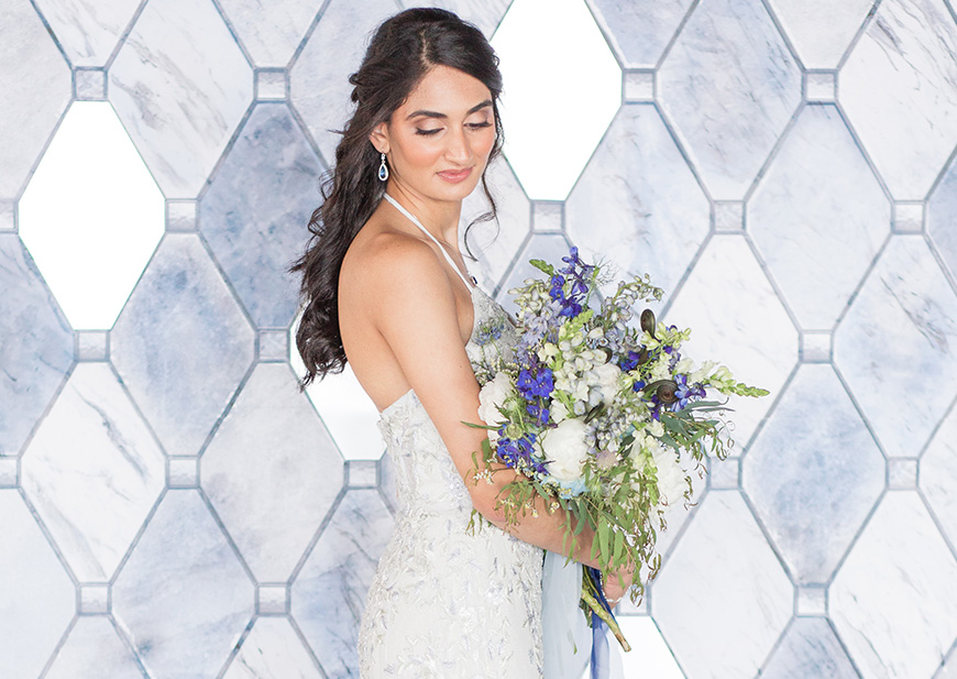 Bride wearing lace halter wedding dress in soft shade of blue with colorful bouquet