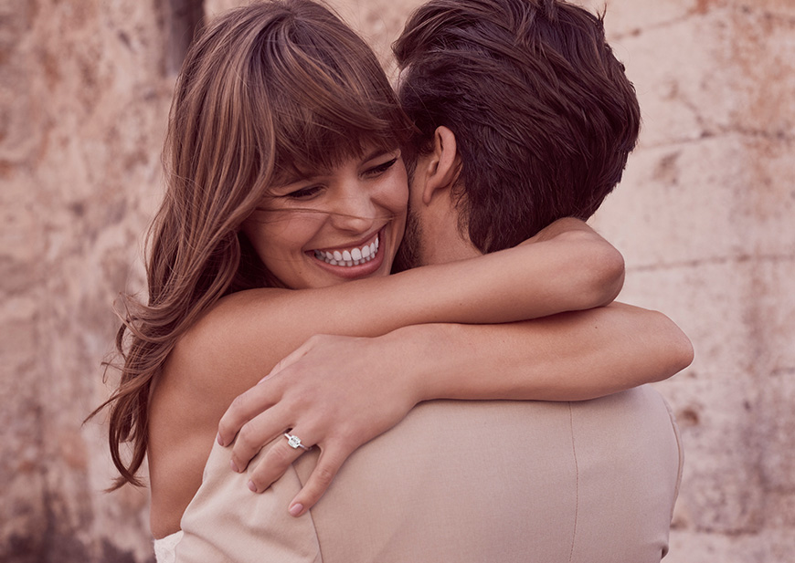 Close-up of bride and groom hugging with smiling bride and wedding ring