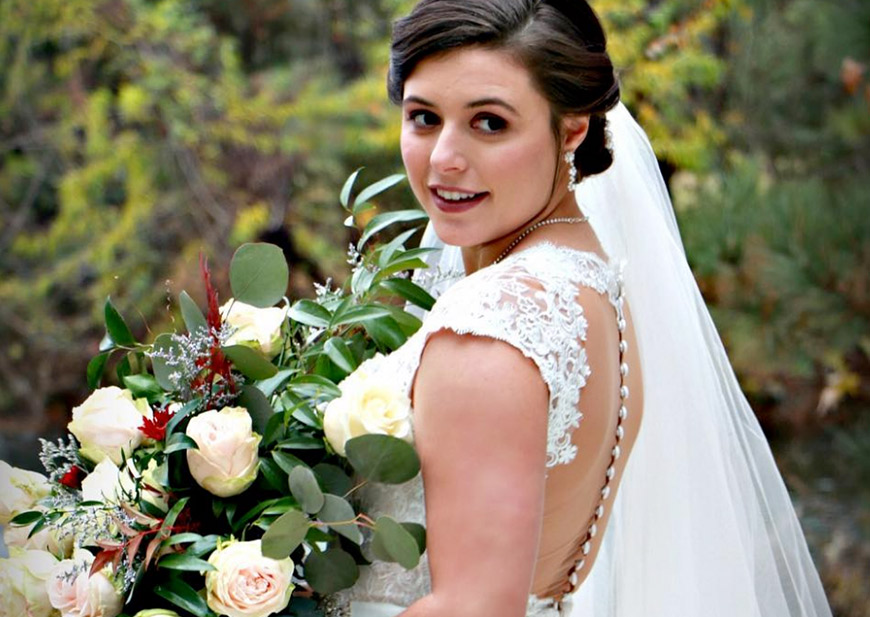 Close-up of real bride wearing flower crown and long sleeve lace wedding dress