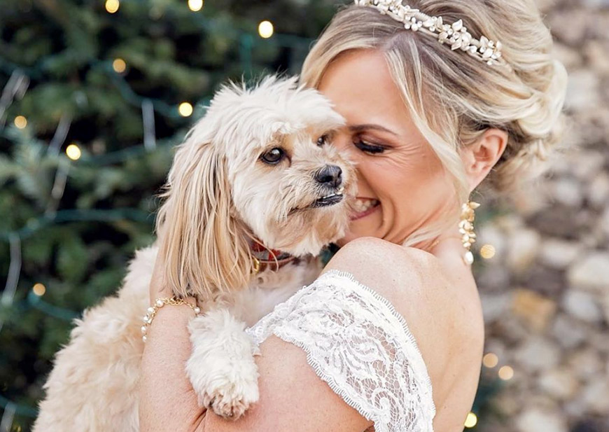 Bride sharing a sweet moment with her dog in front of rustic wood door