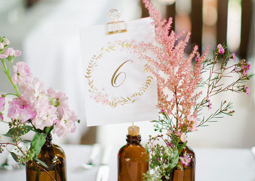 Wedding reception setting with table card and wildflowers in amber vases