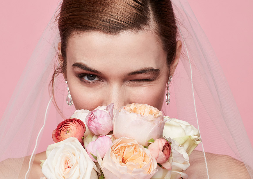 Close-up of winking bride wearing a veil and holding pink floral bouquet