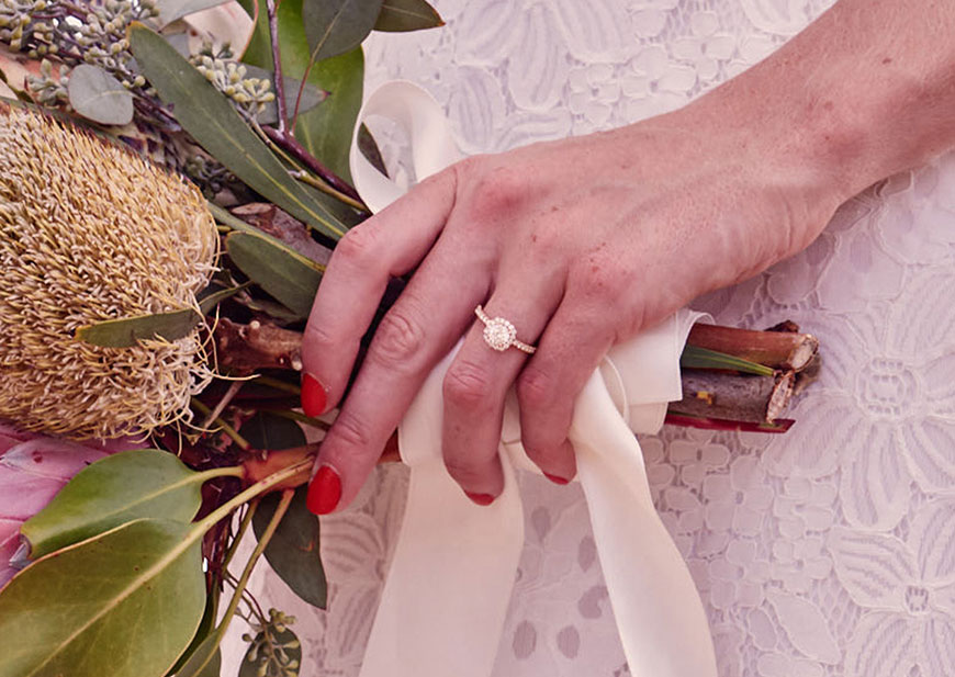 Closeup of bride's hand holding bouquet with diamond wedding ring