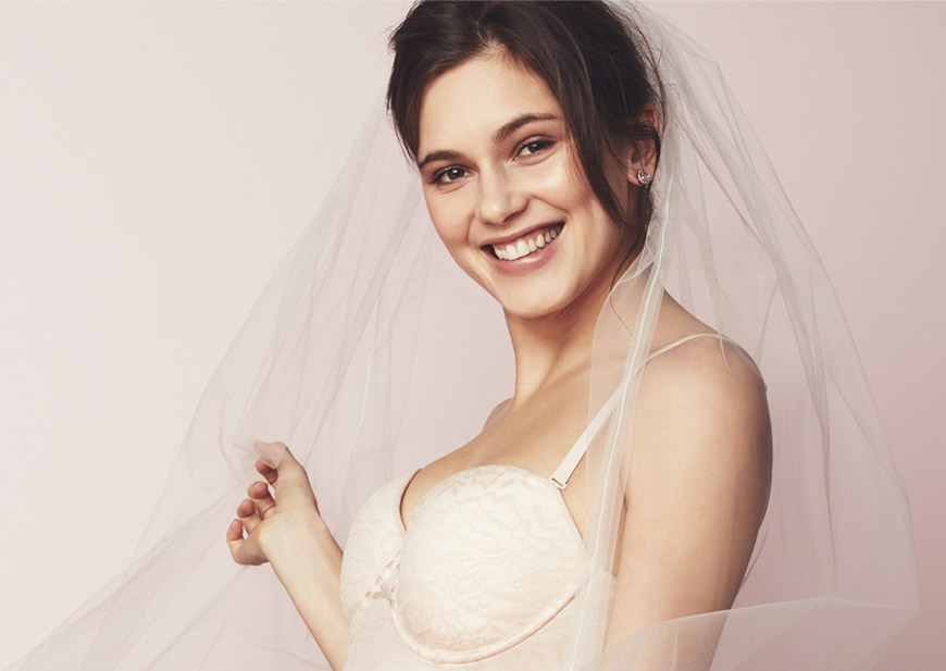 Bride in bra and slip getting dressed in her wedding gown