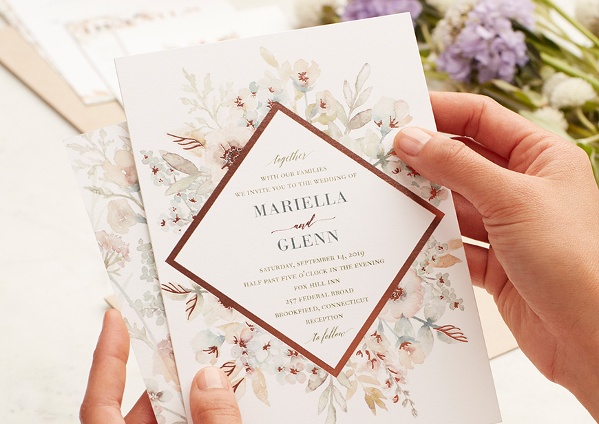 Hand holding wedding Invitation with floral design and flowers in the background