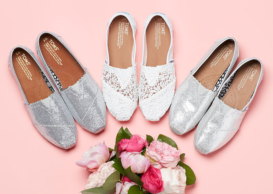 Several pairs of TOMS bridal shoes and flower bouquet