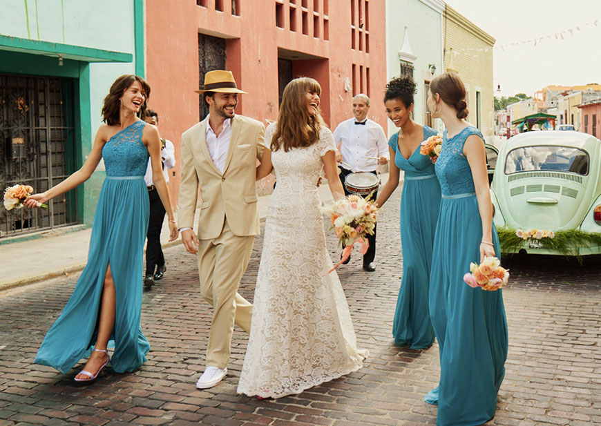Bride and groom and bridesmaids in teal blue dresses walking on cobblestone street