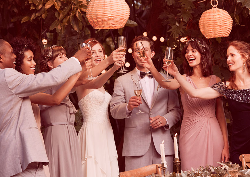 Wedding party toasting wedding day champagne cheers at outdoor setting