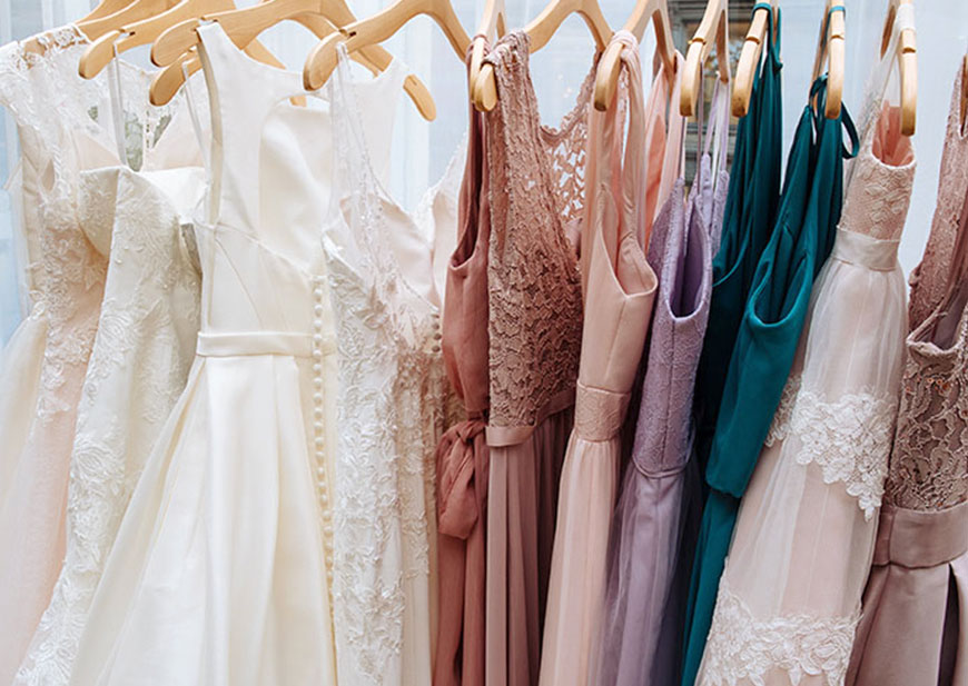 Rack of wedding dresses and bridesmaid dresses on hangers in showroom