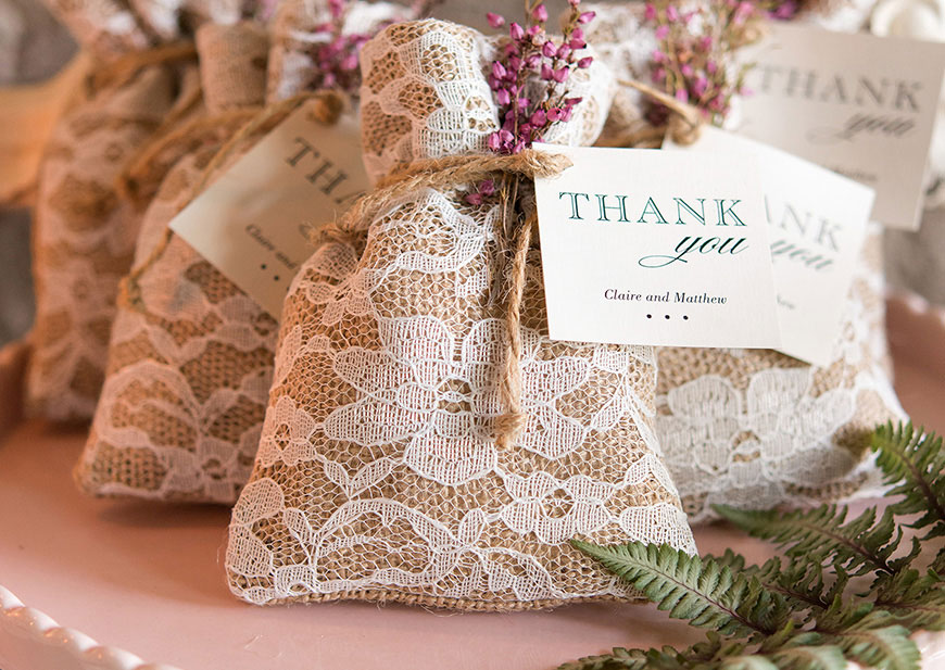 Lace burlap wedding favor bags with personalized tags and rustic ties