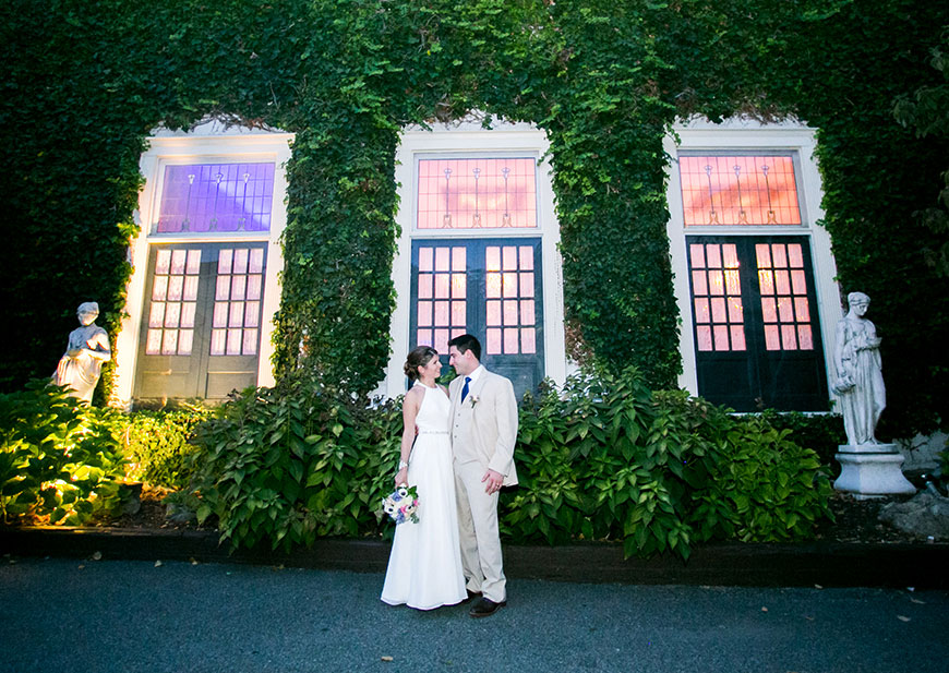 Bride and groom embracing in front of lush wedding venue with tall windows