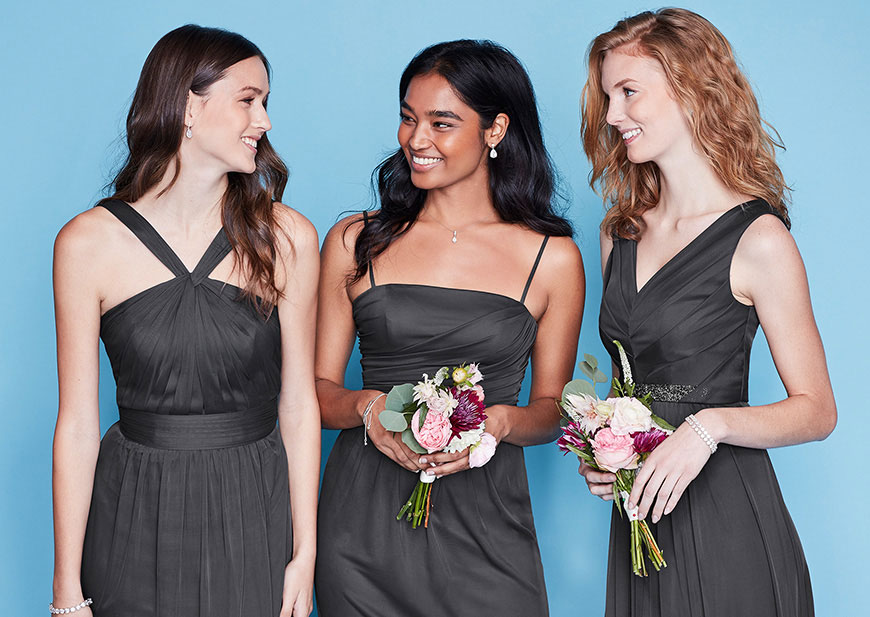 Three bridesmaids in black dresses designed to mix and match