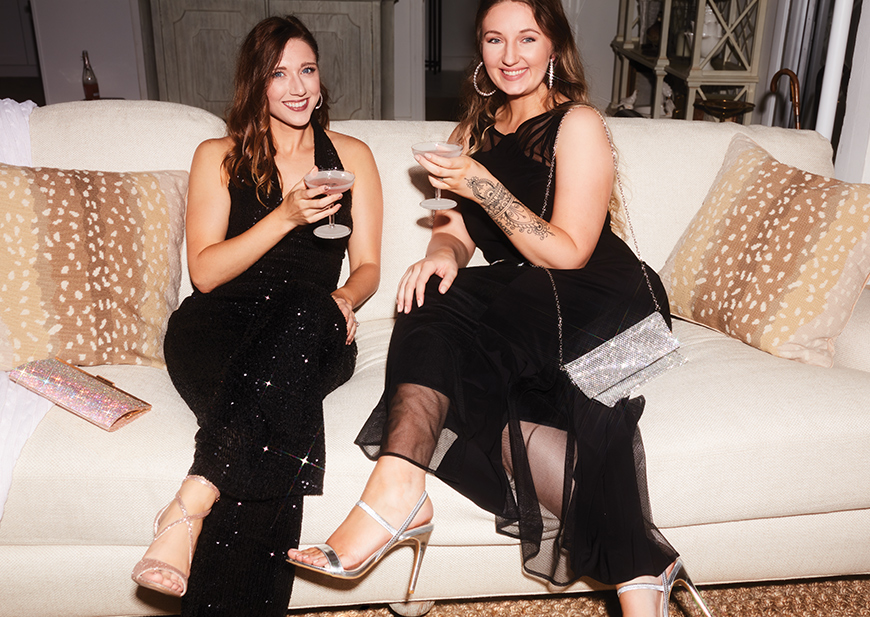 Three party goers wearing special occasion dresses and drinking cocktails on a sofa
