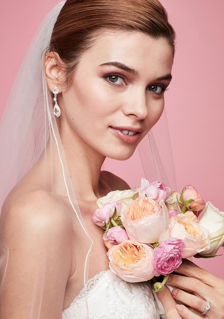 Bride with Cubic Zirconia earrings holding a bouquet of flowers