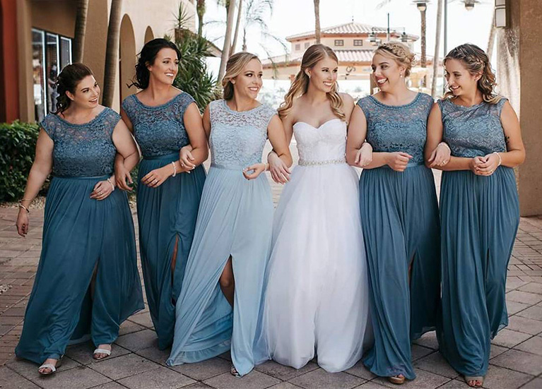 Bride linking arms with blue bridal party